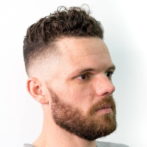 high top curly hair low fade side part hairstyle beard